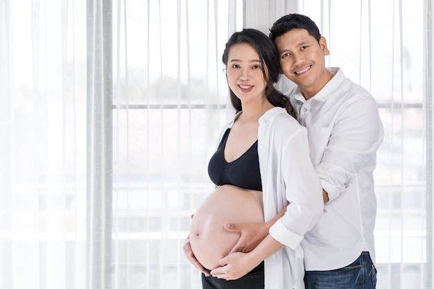 Pregnant woman with husband with window background