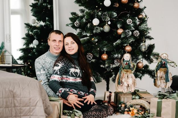 自宅のクリスマスツリーの近くで男性と妊娠中の女性。メリークリスマスとハッピーホリデー!妊娠、休日、人々と期待の概念。
