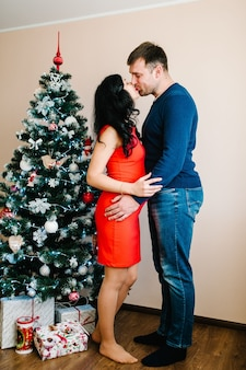 Pregnant woman with man near christmas tree at home. merry christmas and happy holidays! pregnancy, holidays, people and expectation concept.