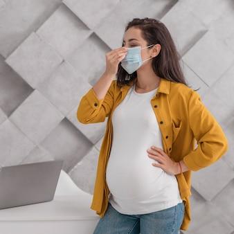 自宅で医療マスクを持つ妊婦