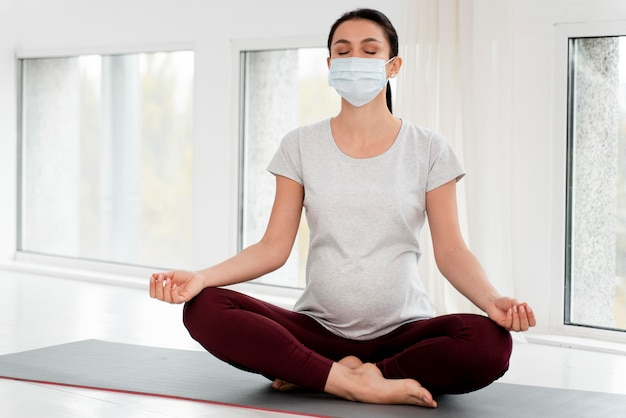 Pregnant woman with medical mask meditating