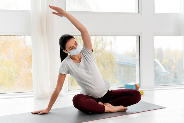 Pregnant woman with medical mask stretching