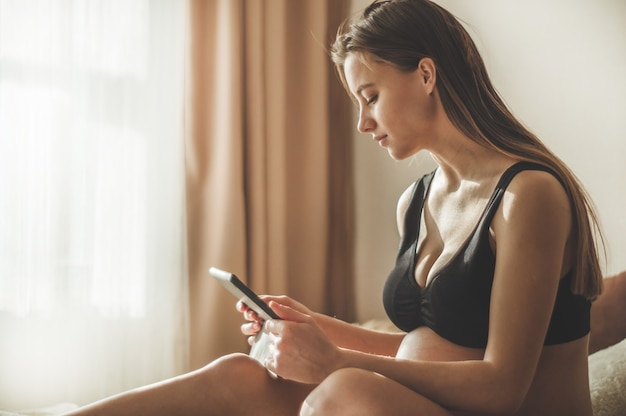 Беременная женщина с современным планшетом сидит на кровати и поправляет длинные волосы