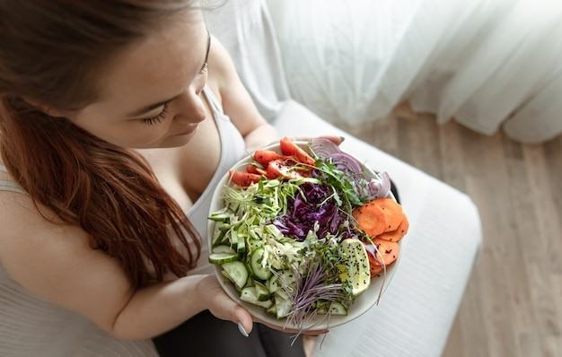 Pregnant woman with a plate of fresh vegetable salad at home on the couch top view.