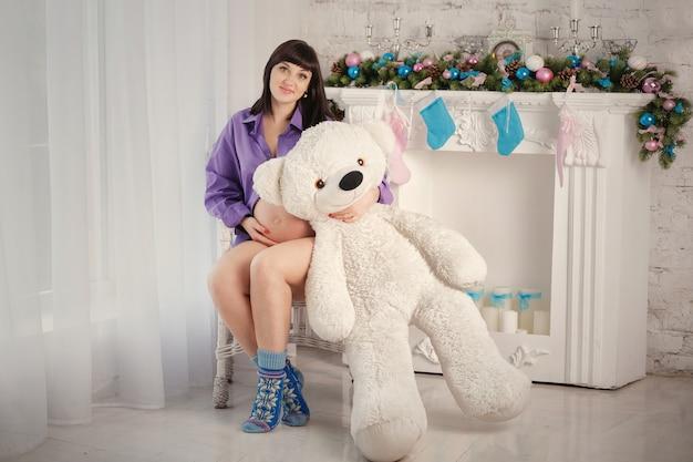 The pregnant woman with a polar teddy bear sits near a fireplace