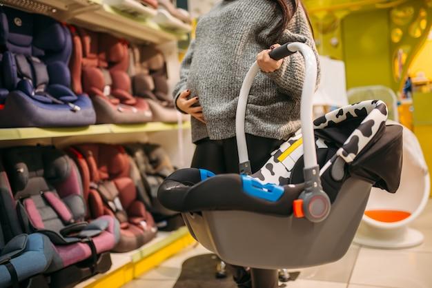 Беременная женщина с портативной кроватью, выбирая детское автокресло в магазине. товары для безопасной перевозки детей