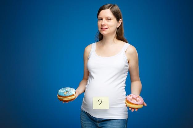 Беременная женщина со знаком вопроса на животе и двумя пончиками с розовой и голубой глазурью на гендерной вечеринке