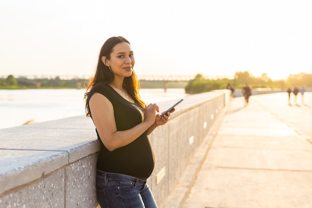 야외에서 스마트폰으로 임신한 여자입니다. 임신, 기술 및 통신 개념