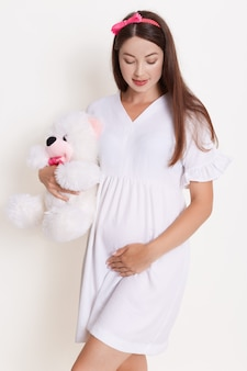 Pregnant woman with teddy bear wearing beautiful dress