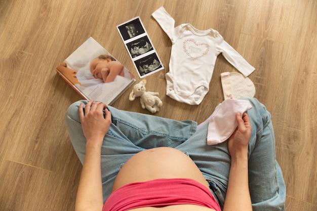妊娠中の出産の準備をしている白い赤ちゃんのボディスーツ、靴下、帽子の超音波画像を持つ妊婦。床に座っている若い母親