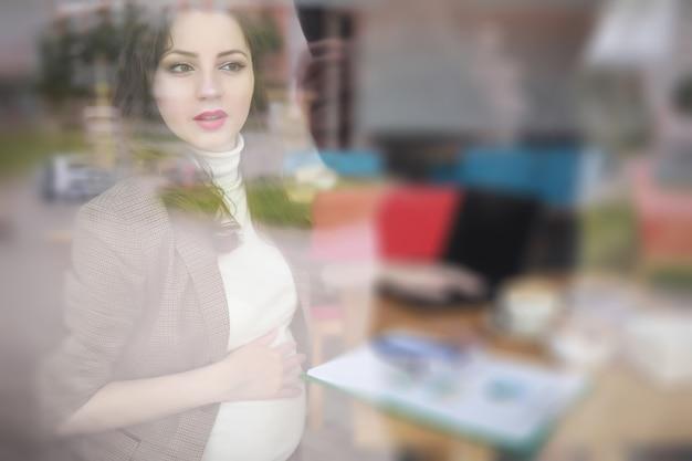 カフェのコンピューターで昼食時に働く妊婦