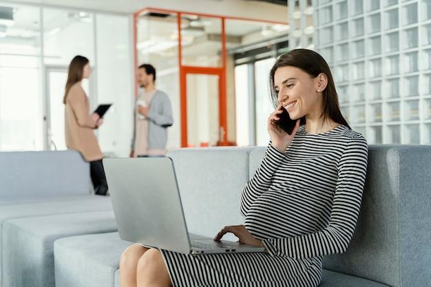 Donna incinta che lavora in ufficio