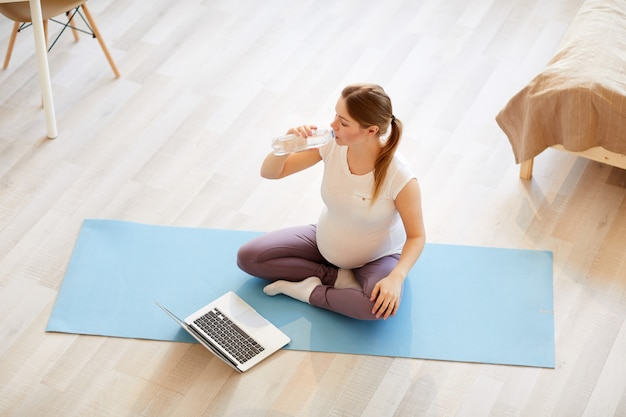 Pregnant woman working out at home top view