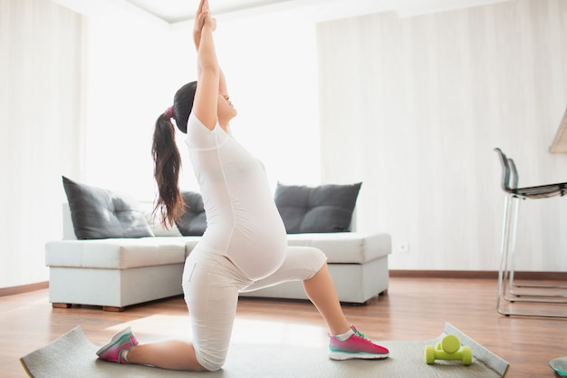 A pregnant woman works out on a yoga mat at home. pregnancy and sports. yoga and pilates for pregnant women. third trimester of pregnancy