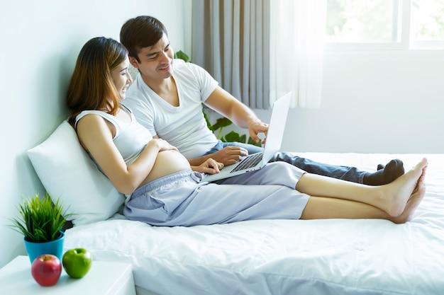 임산부와 남편은 게으른 아침에 쇼핑을 위해 노트북을 사용하여 침대에서 일하고 있습니다.
