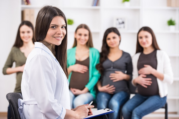Pregnant women are listening to doctor.