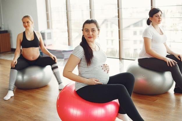 ジムでヨガをしている妊娠中の女性