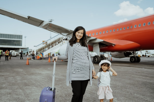 Pregnant women and his daughter like to stand beside the plane
