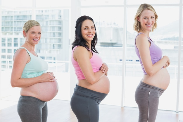 Pregnant women standing in a line smiling at camera