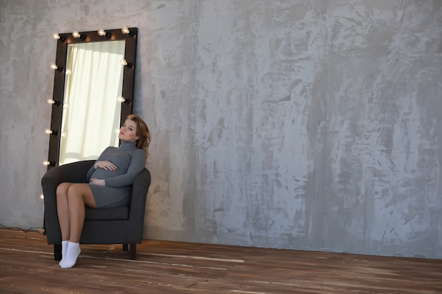 Беременная молодая и красивая девушка в домашних условиях позирует