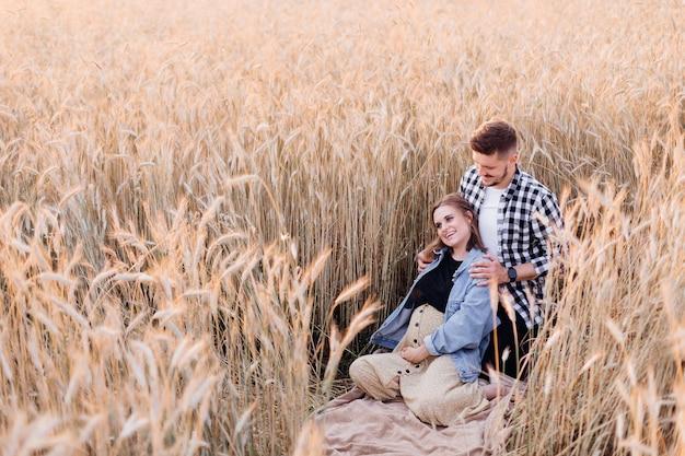 임신한 젊은 부부는 여름 저녁에 시리얼 식물 사이에서 자연을 즐깁니다. 가족과 임신. 사랑과 부드러움. 행복과 평온. 새로운 삶을 돌봅니다.
