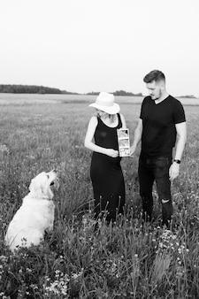 임신한 젊은 부부는 여름 저녁 산책을 하는 개에게 태어나지 않은 아이의 초음파를 보여줍니다. 흑백 사진. 아이를 기다리고 있습니다. 임신 관리. 현대 검사 방법.