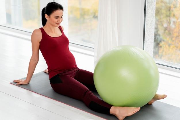 Беременная молодая женщина, тренирующаяся