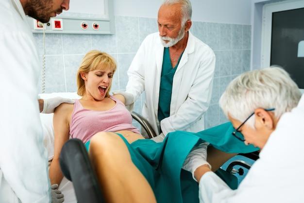 임신한 젊은 여성이 병원에서 출산을 위해 밀어붙이고, 산부인과 의사가 도움을 줍니다.
