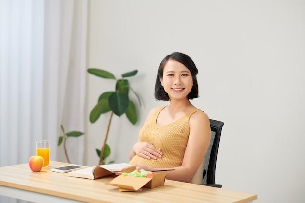 Беременная молодая женщина сидит и использует цифровой планшет на столе в гостиной, завтракает и работает