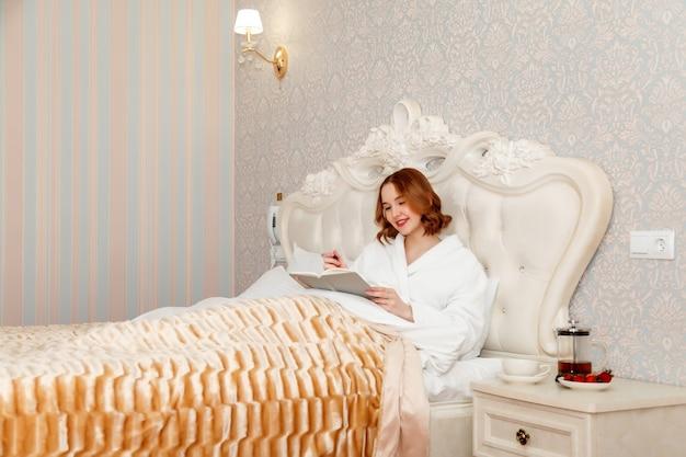 볼펜과 메모장 호텔 방에 침대에 누워 목욕 가운에 임신 한 젊은 여자 슬라브 모습.