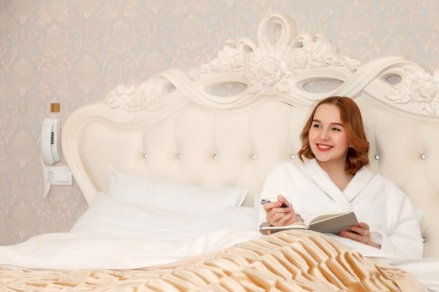 Беременная молодая женщина славянской внешности в халате, лежа на кровати с шариковой ручкой и блокнотом в гостиничном номере.