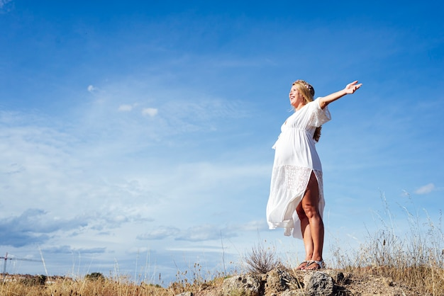 妊娠中の若い女性が腕を伸ばして、笑顔