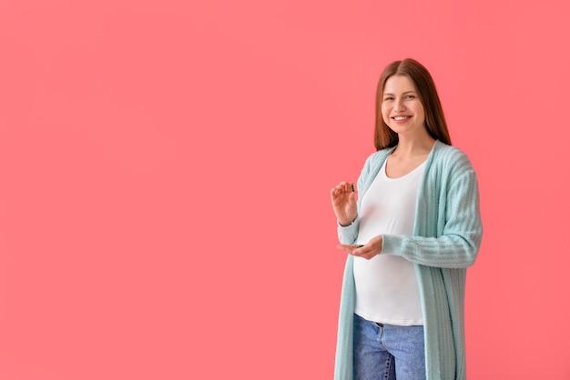 Беременная молодая женщина с таблетками на цветной поверхности