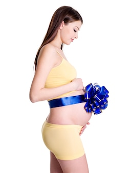 Pregnant young woman with ribbon on her belly as a gift on white