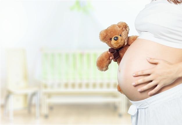 Беременная молодая женщина с плюшевым мишкой на фоне светлой комнаты