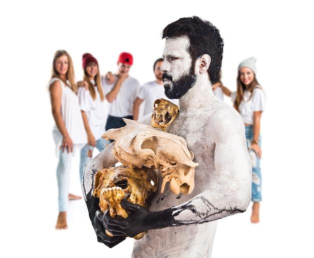 Доисторический мужчина, держащий черепа животных