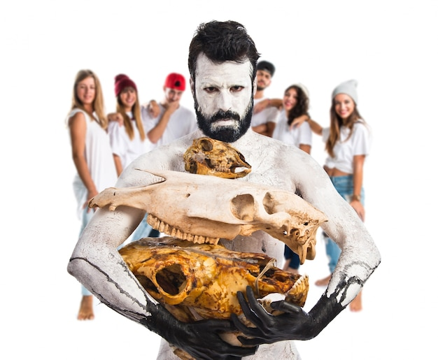 Prehistoric man holding animal skulls