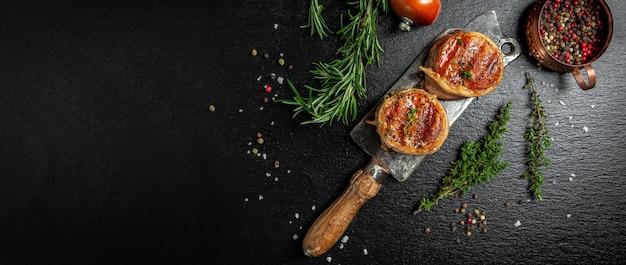 Премиум стейк из говядины. порция сочного стейка из говяжьей вырезки, покрытого беконом, подается на старом мясном мяснике на темном бетонном фоне со специями. формат длинного баннера. вид сверху.