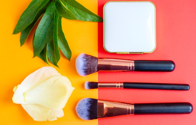 Premium makeup brushes and blush on a colored red and orange background, creative cosmetics flat lay, copy space