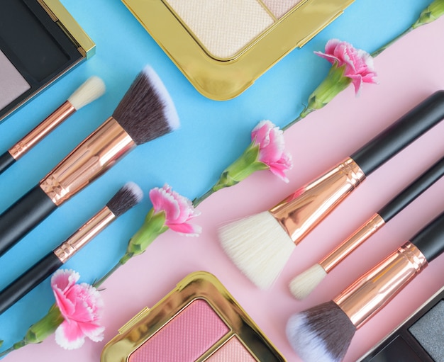 Premium makeup brushes, eye shadow palette and flowers on a colored blue and pink background, creative cosmetics flat lay with diagonal composition