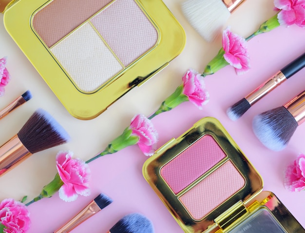 Premium makeup brushes, eye shadow palette and flowers on a colored yellow and pink background, creative cosmetics flat lay with diagonal composition