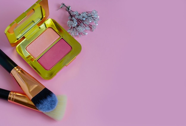 Кисти для макияжа премиум-класса в косметичке, палитра румян на цветном розовом фоне