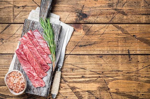 Премиальные редкие ломтики говядины wagyu a5 с высокой мраморной текстурой. деревянный фон. вид сверху. скопируйте пространство.