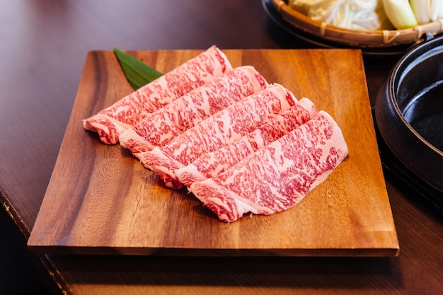 Premium rare slices wagyu a5 beef with high-marbled texture served for sukiyaki and shabu.