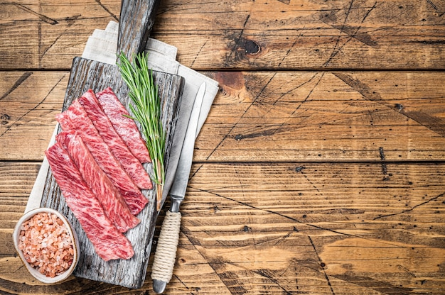 Premium rare slices of wagyu a5 beef with high marbled texture. wooden background. top view. copy space.