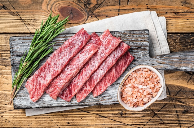 Premium rare slices of wagyu a5 beef with high marbled texture. wooden background. top view.