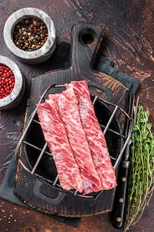 Премиум сырые нарезанные стейки из говядины вагю а5 на гриле для якинику. японская еда. темный фон. вид сверху.