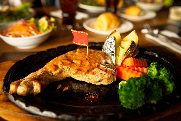 Премиум стейк на косточке на черной матовой тарелке с картофелем и овощами