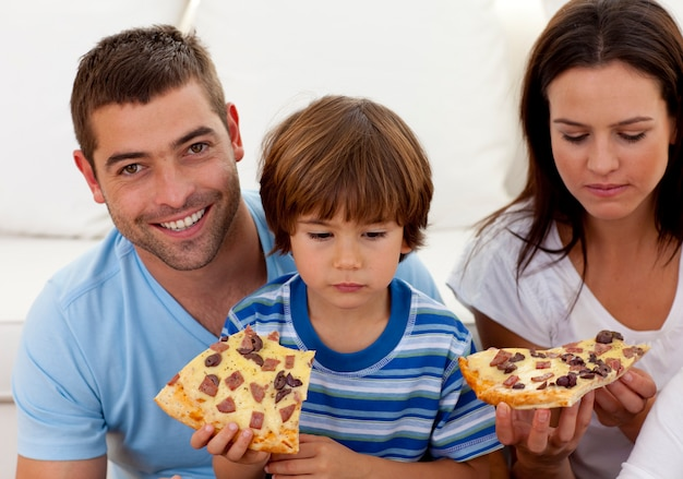 Prents and boy eating pizza in living-room