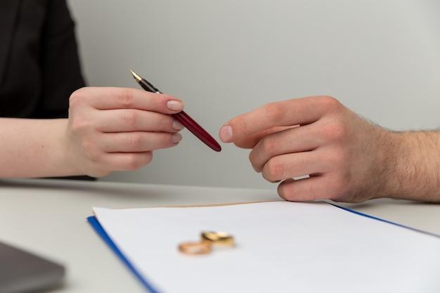 婚前契約の概念。男性と女性が一緒に公証人の文書に署名します。